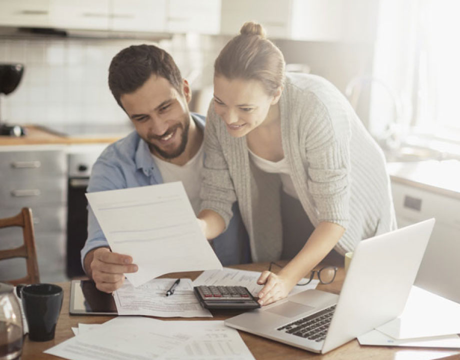 couple smiling while budgeting