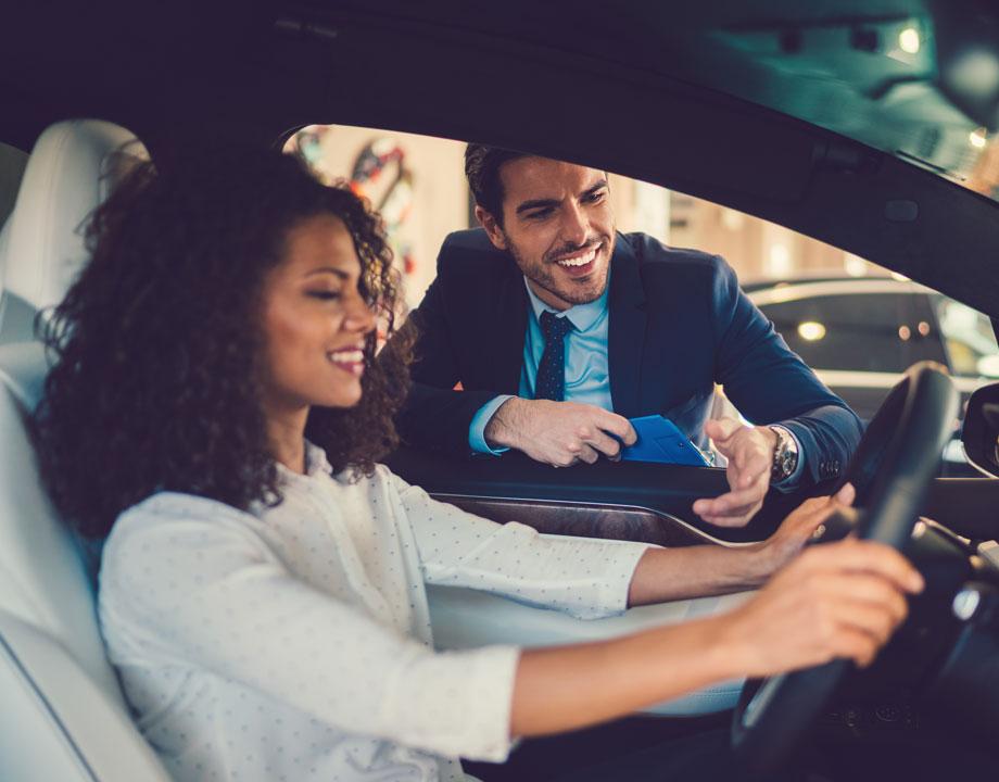 salesman talking to woman about a car