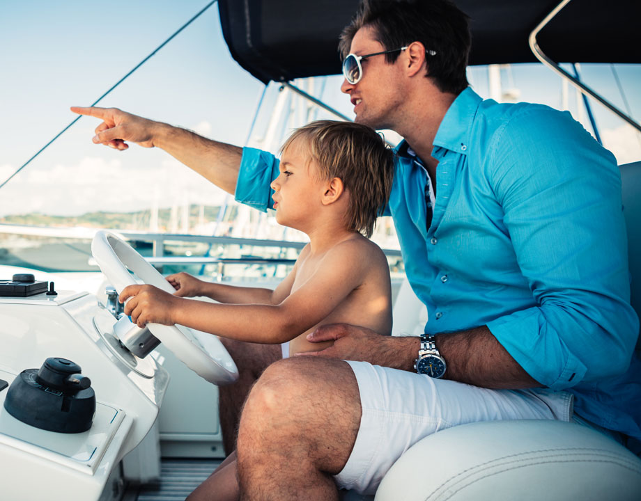 father teaches son to drive a boat